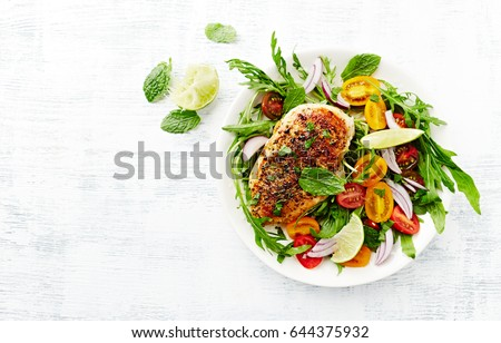 Grilled Chicken Breast on Cherry Tomato and Arugula Salad with Fresh Mint served on white wooden background. Homemade food. Concept for a tasty and healthy meal. Top view. Copy space.  #644375932