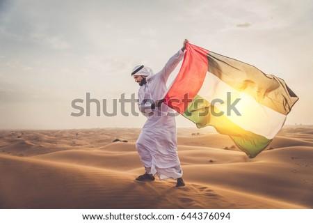 Arabian man walking  in the desert at sunrise Royalty-Free Stock Photo #644376094
