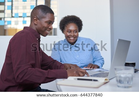 Contemporary dressed African coworkers sitting together at a table in a modern office working online with a laptop #644377840