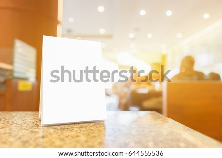 Mock up Menu frame on Table in Bar restaurant ,Stand for booklets with white sheets of paper acrylic tent card on cafeteria blurred background