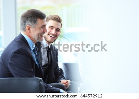 Mature businessman using a digital tablet to discuss information with a younger colleague in a modern business lounge #644572912
