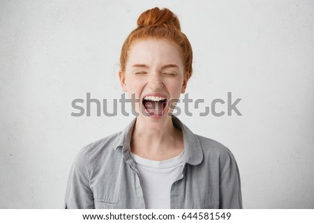 Naughty spoiled teenage girl with ginger hair went into hysterics after mother didn't allow her to go out with friends, closing eyes tight and opening mouth in shriek expressing protest, disobedience #644581549