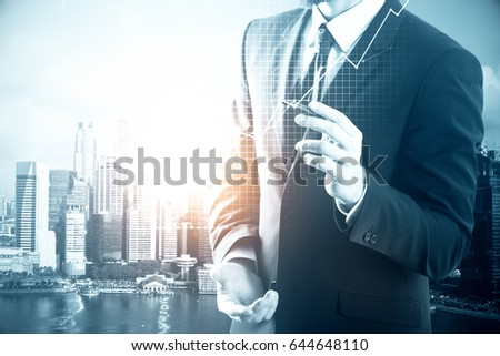 Businessman drawing business chart on city background. Financial growth concept #644648110