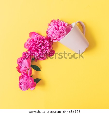 Creative layout made of coffee or tea cup with pink flowers on yellow background