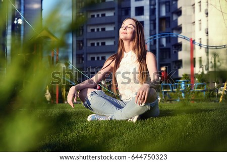 Young woman sitting in lotus position on the lawn in the courtyard of a residential block #644750323