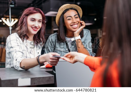 multicultural young girls shopping and paying with credit card in boutique, fashion shopping girls concept #644780821