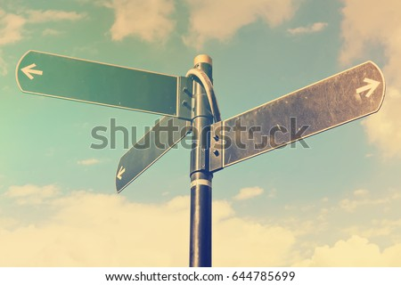 Blank directional road signs against blue sky. Black metal arrows on the signpost. Warm toned colors.  Old style image