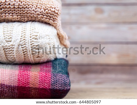 stack of clothes from knitted knitwear on a wooden background #644805097