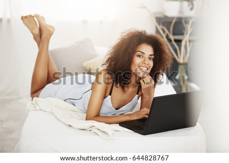Happy beautiful african girl in sleepwear lying with laptop on bed at home smiling looking at camera. #644828767