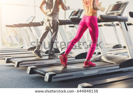 Male and female legs run on treadmills. Man and woman cardio workout in fitness club, crop. Healthy lifestyle, training in gym. Flare effect #644848138