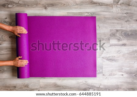 Woman rolling her Yoga mat after a workout - top view Royalty-Free Stock Photo #644885191