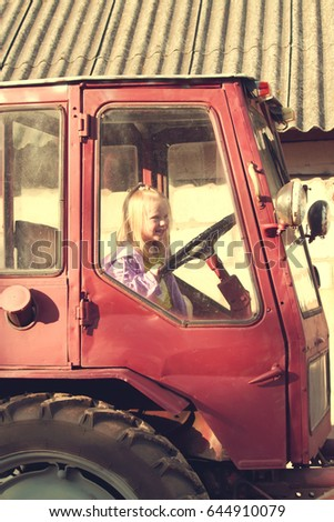 Little girl hold sitting in the tractor cab #644910079
