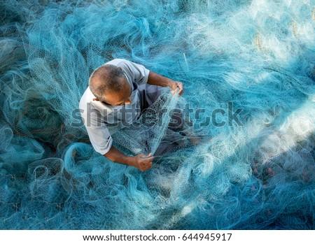 Old Fishermen are repairing fishing nets.Fishermen are cleaning fishing nets.Thailand Royalty-Free Stock Photo #644945917