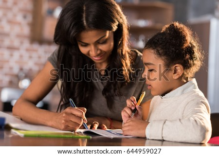 Mother and cute little daughter sitting at table and doing homework together at home, homework help concept #644959027
