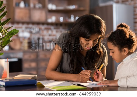 Mother and cute little daughter sitting at table and doing homework together at home, homework help concept #644959039
