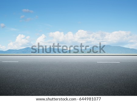 Side view asphalt road on sunny summer day near the mountain . Royalty-Free Stock Photo #644981077