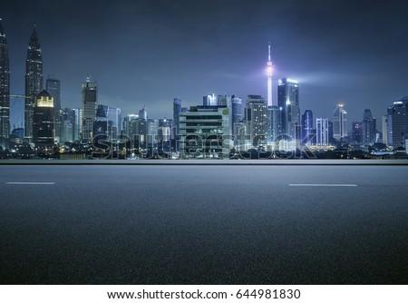 Side view asphalt road on snight scene near the modern city .