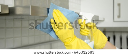 Close up of female hands in rubber protective yellow gloves cleaning the kitchen metal extractor hood with rag. Home, housekeeping concept. Horizontal photo banner for website header design  #645012583