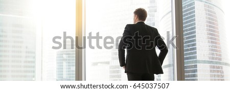 Full length back view of successful businessman in suit standing in office with hands on  waist, CEO looking through window. Horizontal photo banner for website header design with copy space for text