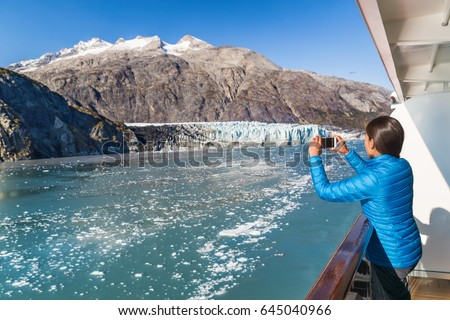 Alaska cruise tourist taking photo of Glacier Bay. Ship passenger on balcony looking at view taking smartphone pictures of Margerie glacier from boat. Woman using phone app on travel vacation.