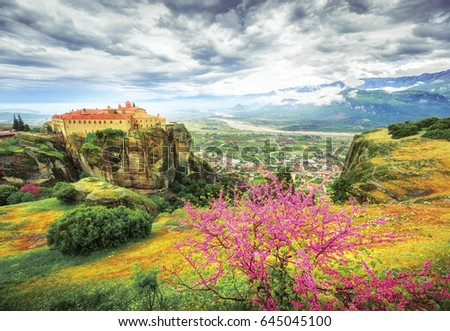 Meteora monasteries in Greece, spring scenery with red blooming tree in foreground, fantastic epic sky in background. #645045100