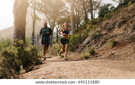 Young people trail running on a mountain path. Two runners working out in morning. #645111880