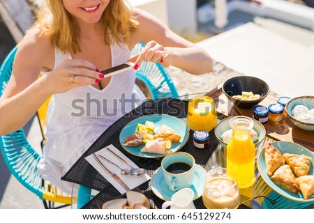 Woman taking picture of food with mobile phone
