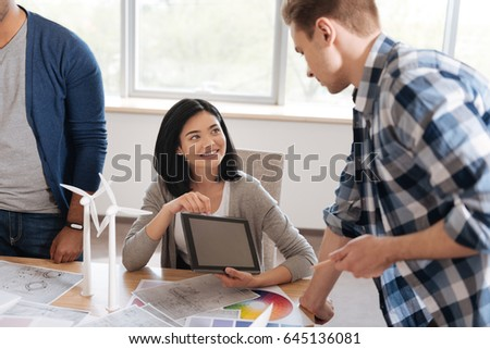 Pleasant pretty woman showing her colleague a picture #645136081