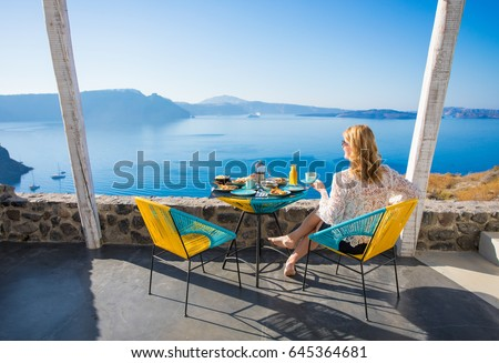 Woman enjoying breakfast with beautiful view from terrace Royalty-Free Stock Photo #645364681