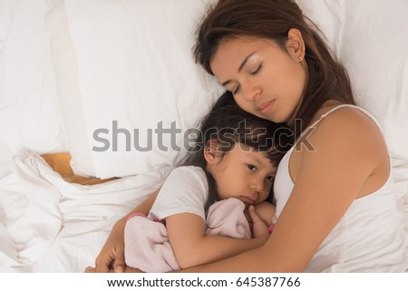 Cute little girl sleeping with mother in bed #645387766