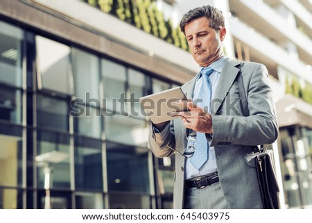Handsome mature businessman in classic suit using a digital tablet. #645403975