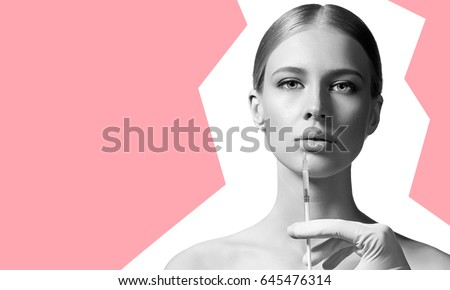 Young woman making anti-aging injections to increase the lips isolated on white background #645476314