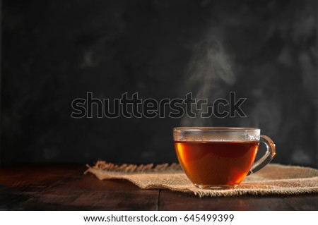 A Cup of freshly brewed black tea,escaping steam,warm soft light, darker background. Royalty-Free Stock Photo #645499399