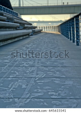 COLOGNE, GERMANY, DECEMBER 30, 2016, Trails of bikes and footsteps on a frozen quay along river Rhine, Cologne. 30 December 2016 #645615541