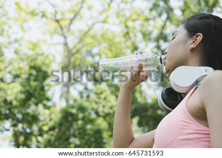young beautiful asian fitness athlete woman drinking water after work out exercising at summer green park. Concept of healthy lifestyle #645731593