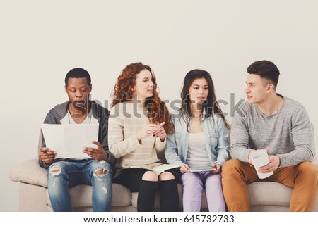 Diverse young students talk, preparing for exam, sitting on sofa in living room and studying, studio shot #645732733