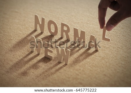 NEW NORMALwood word on compressed or corkboard with human's finger at L letter. Royalty-Free Stock Photo #645775222