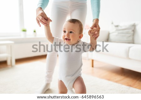 family, child, childhood and parenthood concept - happy little baby learning to walk with mother help at home #645896563