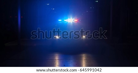 Police car with their lights on flashing red and blue at night.