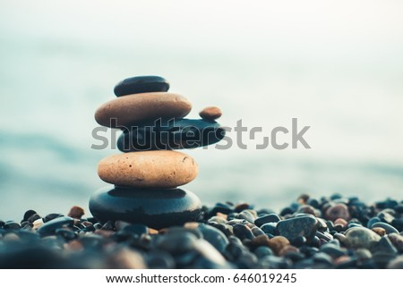 Stones pyramid on pebble beach symbolizing stability, zen, harmony, balance. Shallow depth of field. #646019245