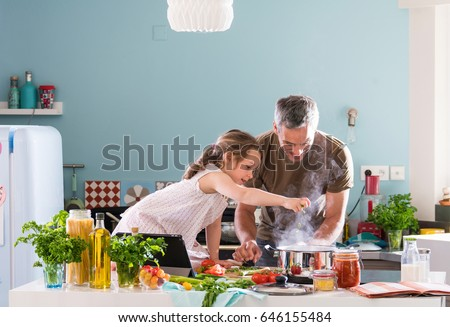 Daddy and his little daughter cooking bolognese sauce for spaghetti in the kitchen, there is steam escaping from the pan on cooking plate Royalty-Free Stock Photo #646155484