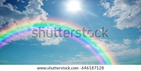 Vivid Rainbow Sky Website Banner  -  Wide blue sky with pretty clouds, a bright sun shining center top and a large rainbow arcing from left to right with copy space Royalty-Free Stock Photo #646187128