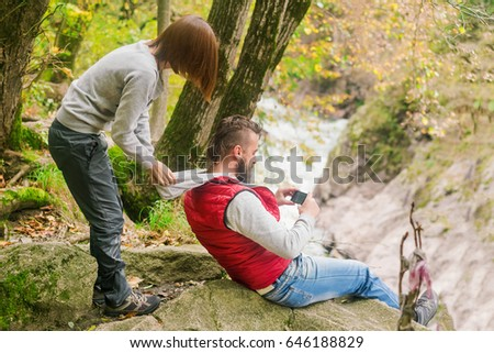 Young woman and man are photographed on the phone at the edge of the mountain #646188829