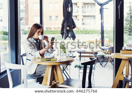 Beautiful Young Woman Drinking Coffee and Looking at her phone #646275766