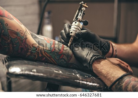 close up tattoo machine. Man creating picture on hand with it in salon #646327681