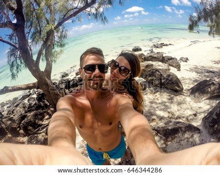 Beautiful young couple taking a selfie on the beach, enjoying their honeymoon. Turquoise ocean water in the background.