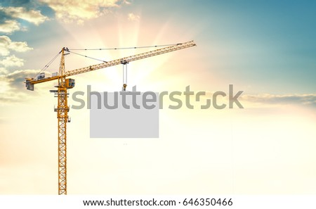 The tower crane lifts the white plate. An empty space for your content. Beautiful sunset or sunrise in the background #646350466