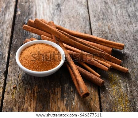 Cinnamon sticks and cinnamon powder on wood #646377511
