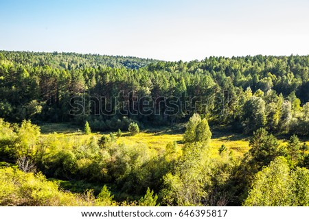Journey on foot through uncharted roads of a national Park. Summer in the forest. Panorama of the natural landscape. The bend of the river and wild nature of Russia. Blue sky. #646395817