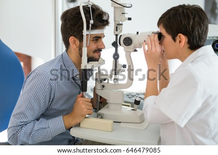 Patient or customer at slit lamp at optometrist or optician #646479085